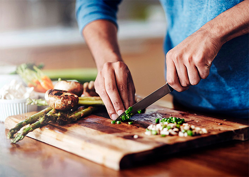 Man chopping green onions on wooden cutting board.