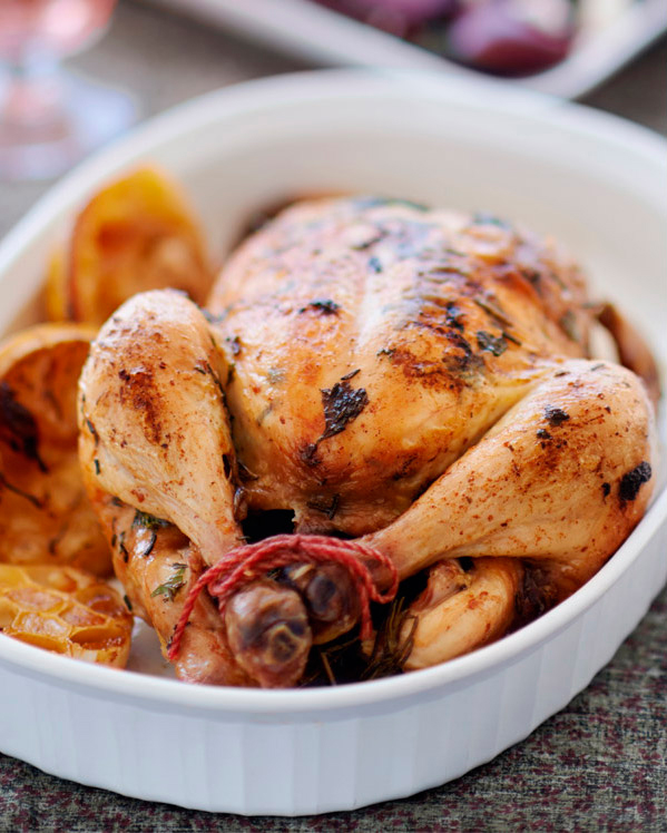 Roast chicken in dish with assorted vegetables.