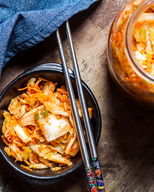 Kimchi sitting in a bowl with chopsticks resting on the rim.