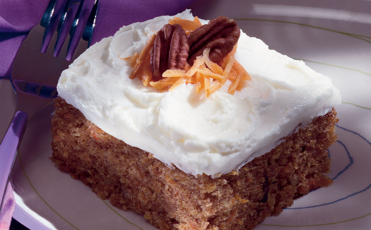 Carrot cake sitting on a plate with a walnut on top and a fork to the side.