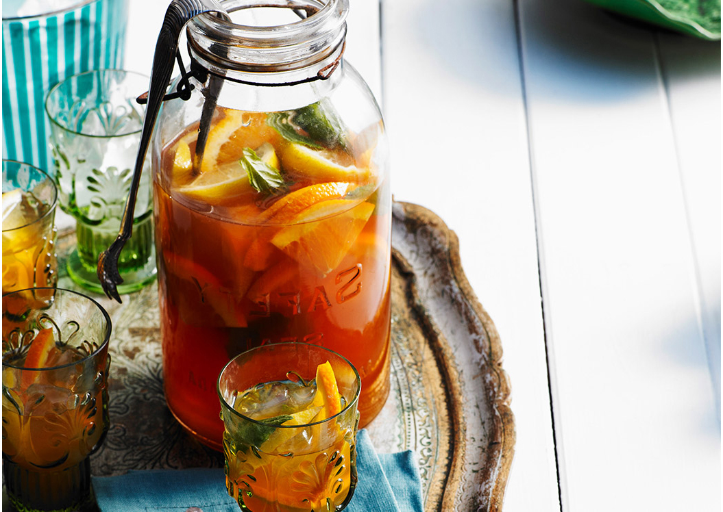 Iced tea in jar with oranges.